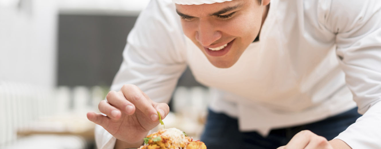 Chef decorating a plate at a restaurant
